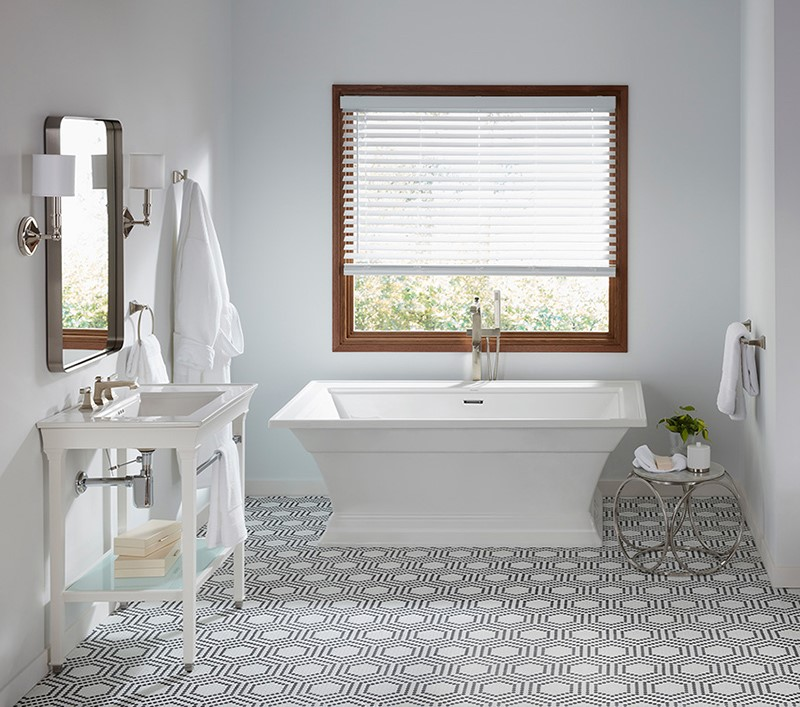 classic fixture light colored bathroom with patterned tile floor